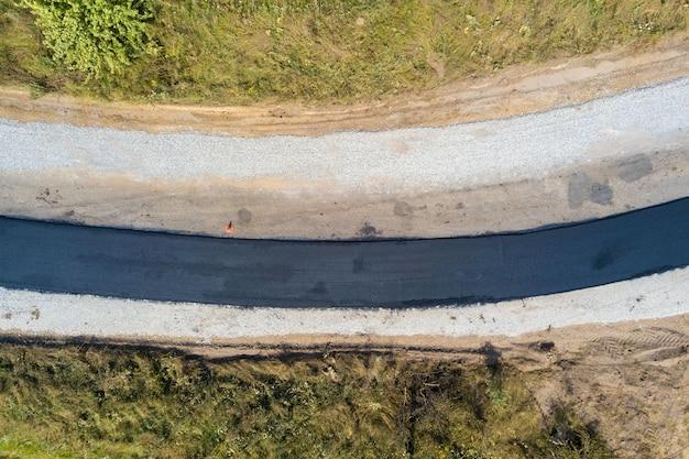 Vue aérienne de la construction d'une nouvelle route avec une voie asphaltée noire nouvellement posée.