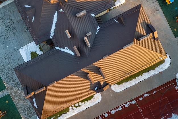 Vue aérienne de la construction d'un toit en tuiles de bardeaux bruns avec une construction de configuration complexe. abstrait, motif géométrique.