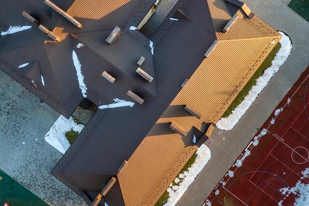Vue aérienne de la construction d'un toit en tuiles de bardeaux bruns avec une construction de configuration complexe.