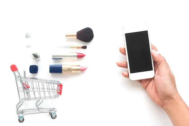 Vue aérienne de cosmétiques et de panier avec une main de femme tenant le téléphone mobile, achats en ligne, vendredi noir