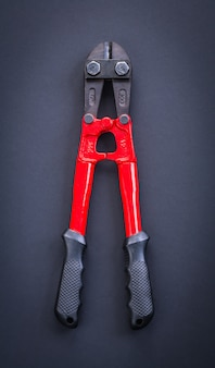 Vue aérienne coupe en acier rouge avec poignées en caoutchouc sur arr.plans noir