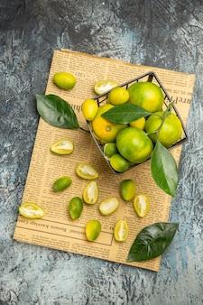 Vue aérienne de coupés en deux kumquats et citrons frais dans un panier noir sur des journaux sur fond gris image stock