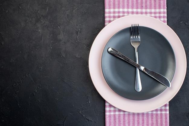 Vue aérienne de couverts en acier inoxydable posés sur des assiettes vides en céramique colorées sur une serviette pliée dénudée rose sur fond noir avec espace libre