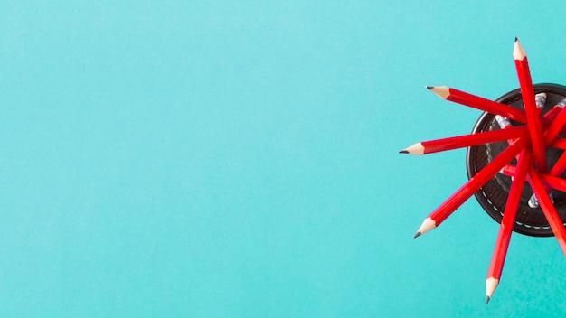 Une vue aérienne de crayons rouges dans le titulaire sur fond turquoise