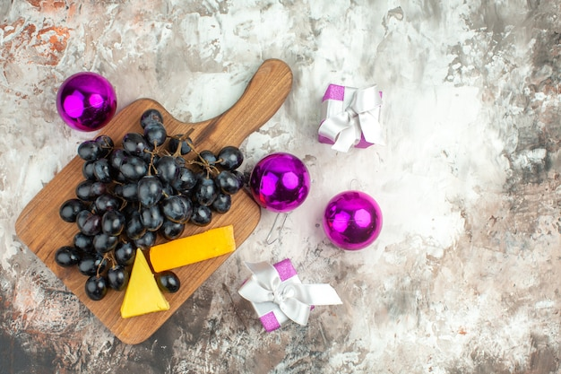 Vue aérienne d'une délicieuse grappe de raisin noir et de fromage sur une planche à découper en bois et des accessoires de décoration de cadeaux sur fond de couleur mélangée