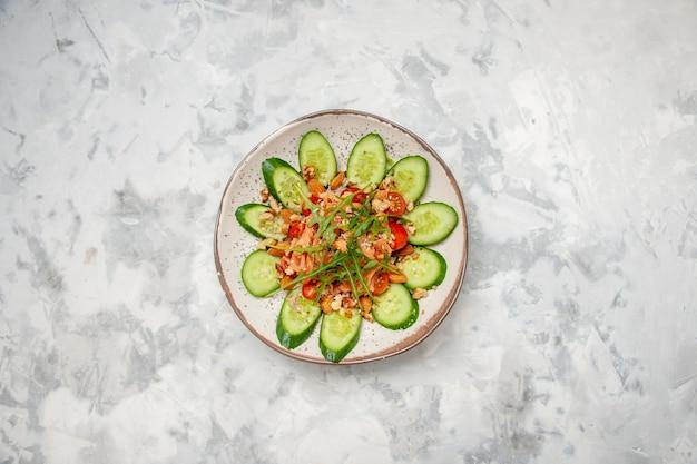 Vue aérienne d'une délicieuse salade décorée de concombre haché et de légumes verts sur une surface blanche tachée avec espace libre