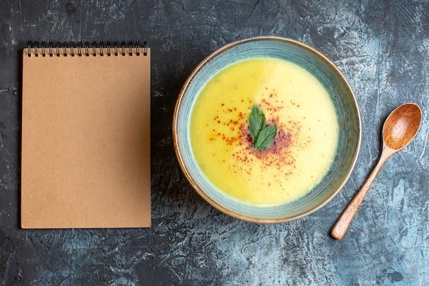 Vue aérienne d'une délicieuse soupe de cahier à spirale servie avec du poivre et de la menthe dans un pot bleu à côté d'une cuillère en bois sur fond sombre