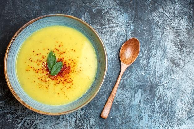 Vue aérienne d'une délicieuse soupe servie avec du poivre et de la menthe dans un pot bleu à côté d'une cuillère en bois sur fond sombre