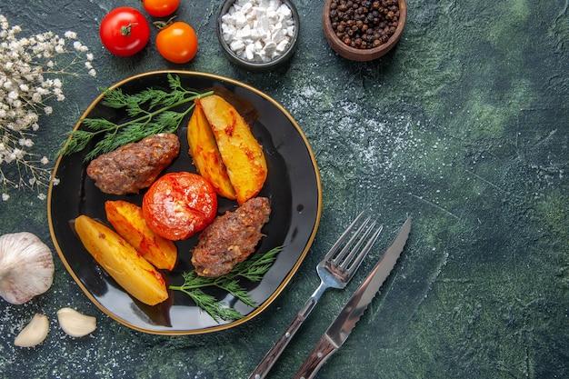 Vue aérienne de délicieuses escalopes de viande cuites au four avec des pommes de terre et des tomates sur une assiette noire ensemble de couverts fleurs blanches épices ails sur fond vert noir couleurs mélangées