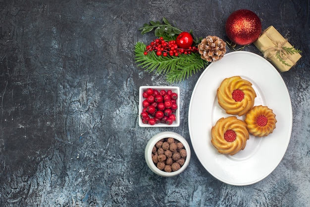Vue aérienne de délicieux biscuits sur une assiette blanche et décorations du nouvel an cadeau cornel dans un petit pot de chocolat sur une surface sombre