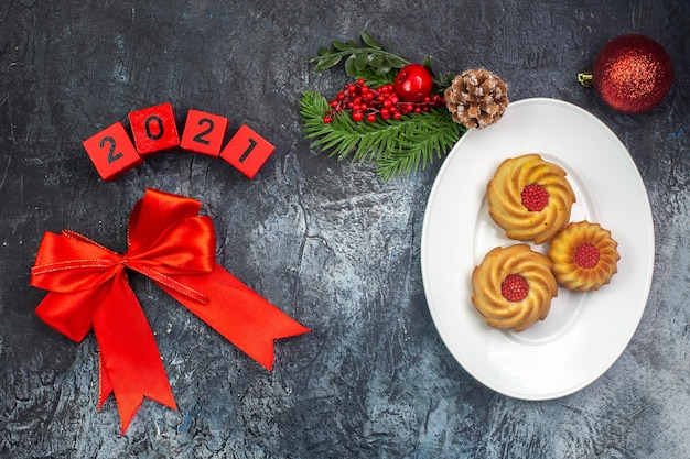Vue aérienne de délicieux biscuits sur une assiette blanche et inscription de décorations du nouvel an sur une surface sombre
