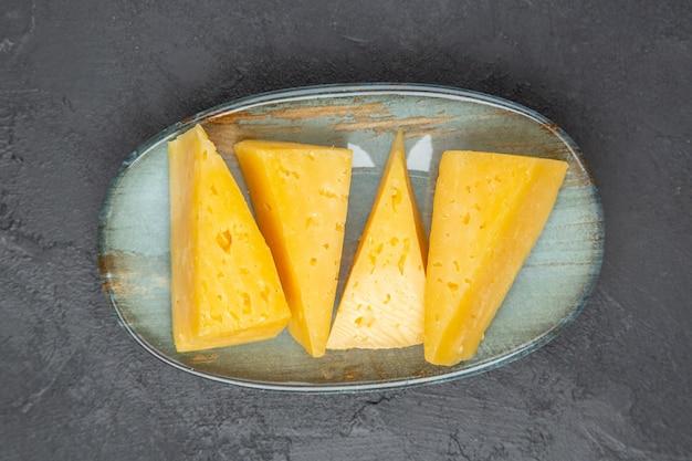 Vue aérienne de délicieux fromages tranchés jaunes sur une plaque bleue sur fond noir