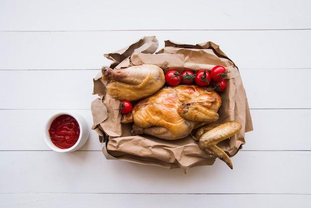 Vue aérienne de délicieux poulet grillé en papier brun avec sauce tomate sur table en bois