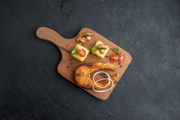 Vue aérienne de délicieux repas de poisson frit et champignons tomates verts sur une planche à découper en bois sur une surface noire
