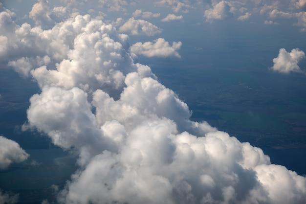 Vue aérienne depuis la fenêtre de l'avion de nuages blancs gonflés par une belle journée ensoleillée.