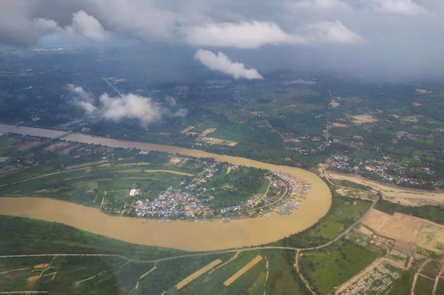 Vue aérienne depuis la fenêtre des avions avec terres agricoles et rivière en jour de pluie nature et transport