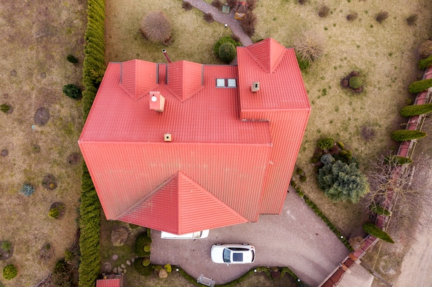 Vue aérienne de dessus du nouveau chalet de maison résidentielle avec toit en bardeaux sur une grande cour clôturée aux beaux jours.