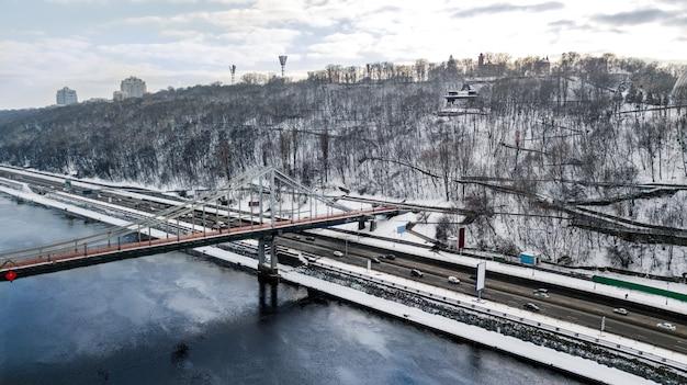Vue aérienne de dessus du pont du parc piétonnier en hiver et le dniepr par le haut, neige paysage urbain de kiev, ville de kiev, ukraine