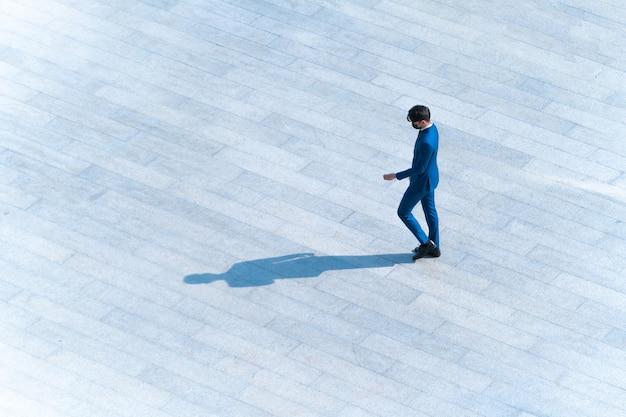 Vue aérienne de dessus les gens d'affaires marchent sur du béton pour piétons avec une ombre sur le sol