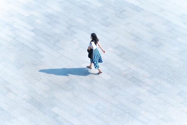 Vue aérienne de dessus les gens marchent sur le béton pour piétons avec une ombre noire sur le sol