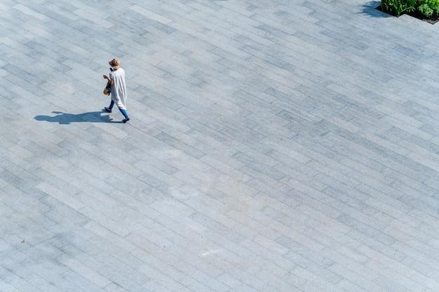 Vue aérienne de dessus les gens marchent sur du béton pour piétons avec une ombre de silhouette noire sur le sol