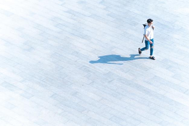 Vue aérienne de dessus l'homme les gens avec un masque facial marchent sur du béton pour piétons