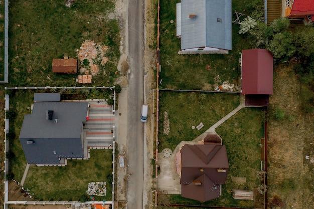 Vue aérienne de dessus d'une maison avec cour pavée avec pelouse d'herbe verte avec sol en béton.