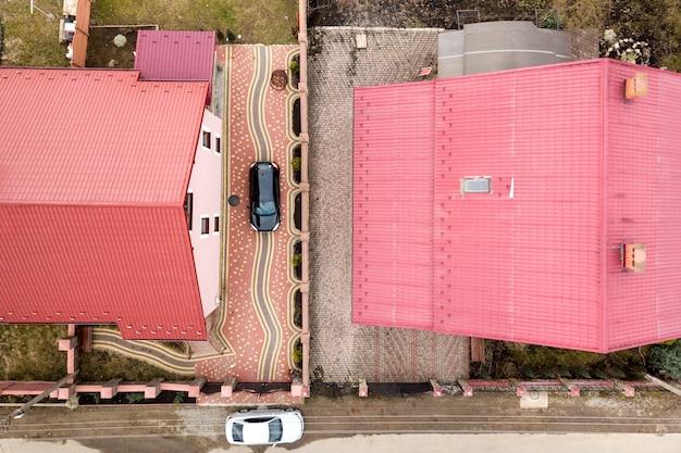Vue aérienne de dessus de maison avec toit en bardeaux et cheminée en brique dans un quartier calme