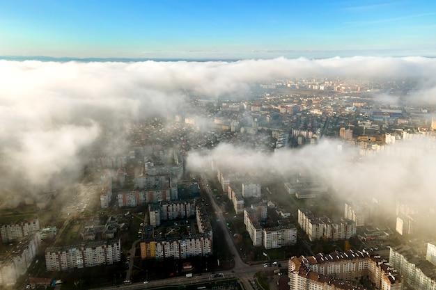 Vue aérienne de dessus des nuages blancs moelleux sur la ville moderne avec des immeubles de grande hauteur.