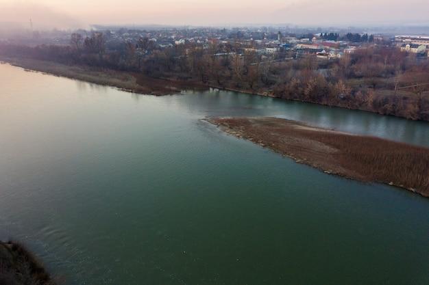 Vue aérienne de dessus, panorama de la campagne de l'eau calme de la rivière et de l'île avec de l'herbe sèche, horizon brumeux sous le ciel bleu par une journée ensoleillée. photographie de drone.
