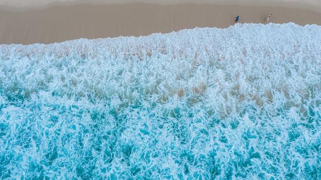 Vue aérienne de dessus de la plage de sable avec les touristes en voyage dans la belle vague de la mer