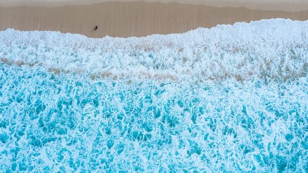 Vue aérienne de dessus de la plage de sable avec des touristes en voyage dans la belle vague de la mer