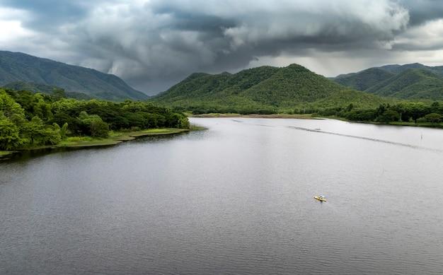 Vue aérienne de dessus de route de campagne dans la forêt verte d'été et le lac bleu