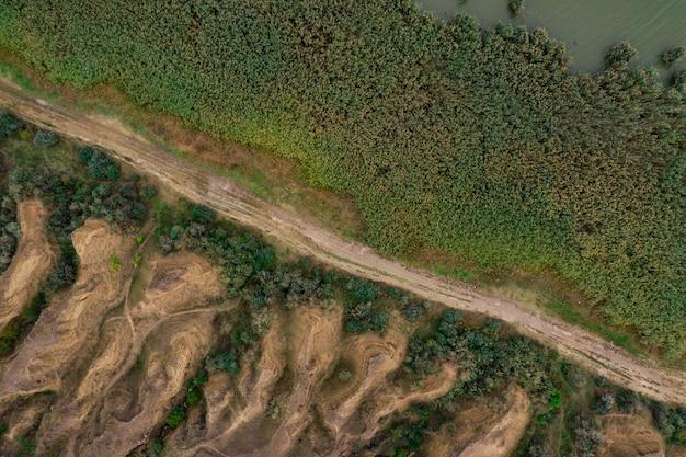 Vue aérienne de dessus de la route de campagne divisant les dunes de sable et de graminées.