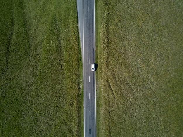 Vue aérienne de dessus de voiture à cheval sur une route droite avec de l'herbe verte des deux côtés