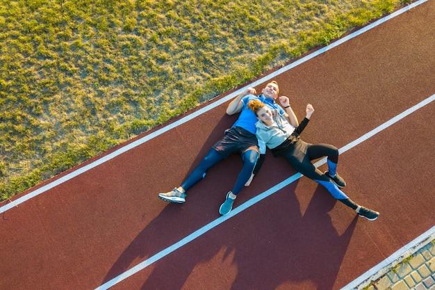 Vue aérienne de deux jeunes sportifs et sportives portant sur la piste de course en caoutchouc rouge d'un stade