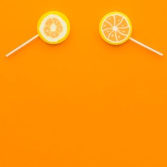 Vue aérienne de deux sucettes aux agrumes sur fond orange