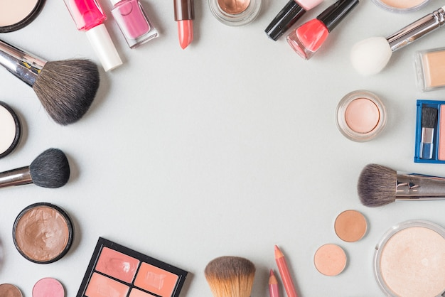 Vue aérienne de divers produits de maquillage formant une forme circulaire sur fond blanc