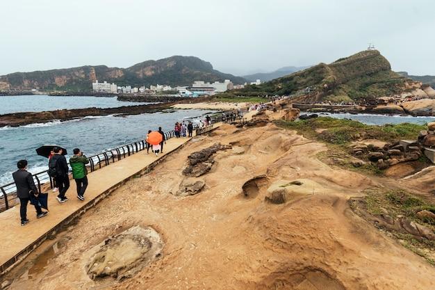 Vue aérienne de la diversité des touristes marchant dans le géoparc de yehliu, un cap sur la côte nord de taïwan. un paysage de rochers en nid d'abeilles et de champignons érodés par la mer.