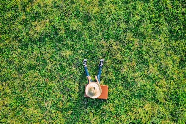 Vue aérienne de drone d'une fille fatiguée avec un chapeau de paille et un jean assis et reposant sur une valise vintage marron sur une prairie d'herbe verte. notion de voyage.