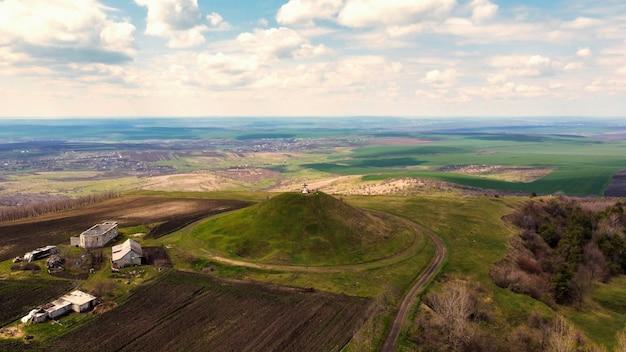 Vue aérienne de drone d'un monticule avec croix sur le dessus en moldavie. champs et villages au loin