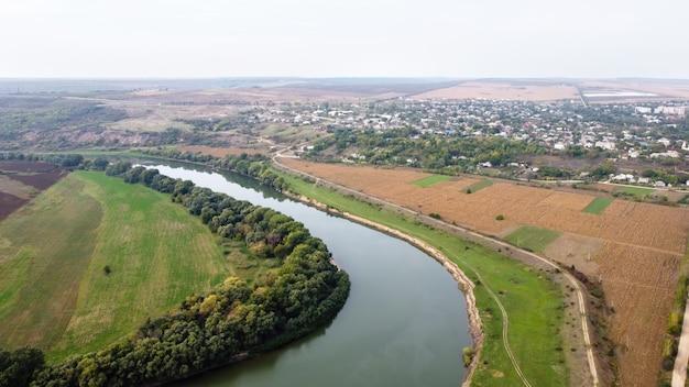Vue aérienne de drone de la nature en moldavie, rivière flottante avec ciel réfléchissant, champs verts avec arbres, brouillard dans l'air