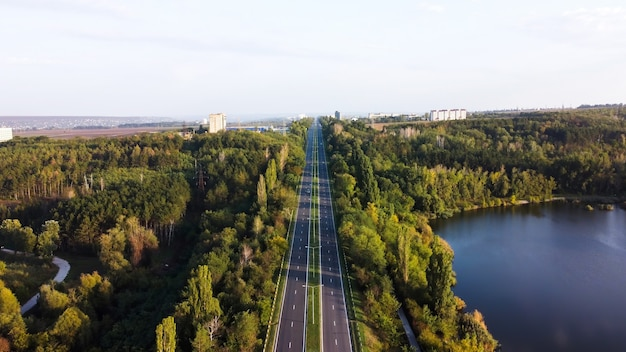 Vue aérienne de drone de la nature en moldavie, route avec un lac et des arbres verts le long d'elle