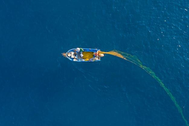Vue aérienne de drone pêcheur attraper du poisson à l'aide de filet à l'océan
