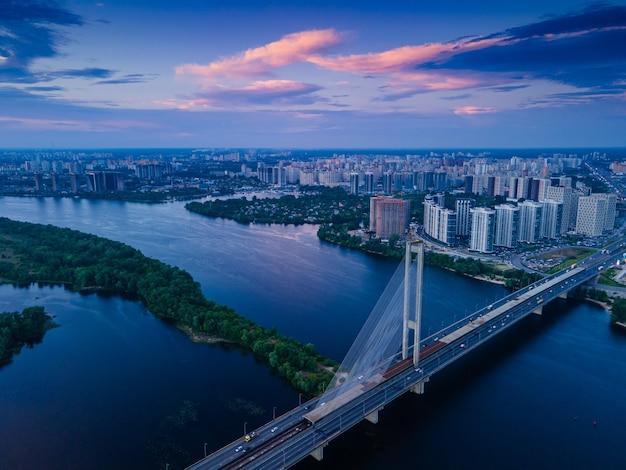 Vue aérienne d'un drone sur un pont à haubans sur une rivière dans une grande ville le soir
