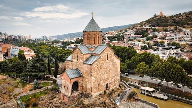 Vue aérienne de drone de tbilissi en géorgie au canal d'eau de l'église metekhi par temps nuageux
