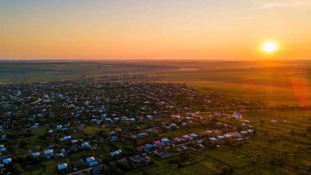 Vue aérienne de drone d'un village en moldavie au coucher du soleil. de vastes champs autour