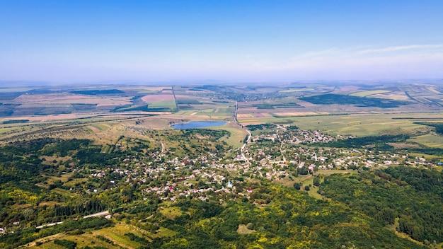 Vue aérienne de drone d'un village en moldavie. larges champs, lac, forêt autour