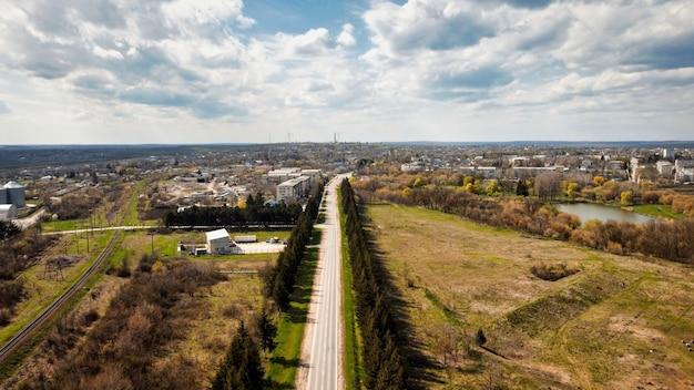 Vue aérienne de drone d'une ville en moldavie. route, vieux immeubles résidentiels, champs alentour, arbres nus