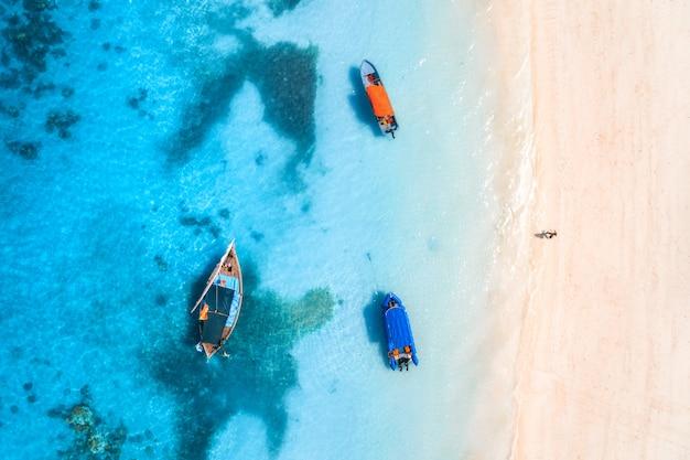 Vue aérienne du bateau de pêche dans l'eau bleu clair au coucher du soleil